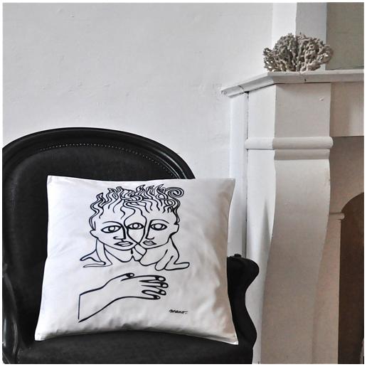 Housse de coussin blanc brodé noir sur fauteuil noir